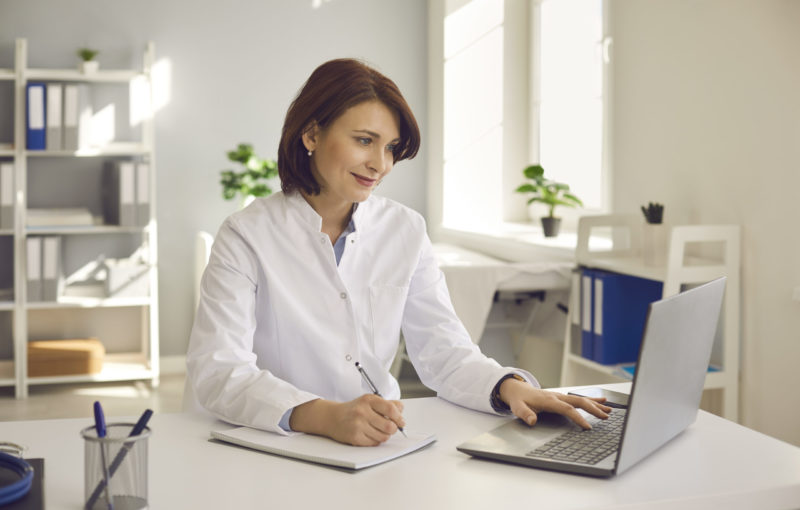 Female doctor writes notes while watching an online medical webinar or training seminar while sitting with a laptop in the workplace. Positive doctor does his best to provide quality medical care